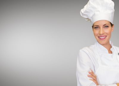 Chef standing with arms crossed against grey background